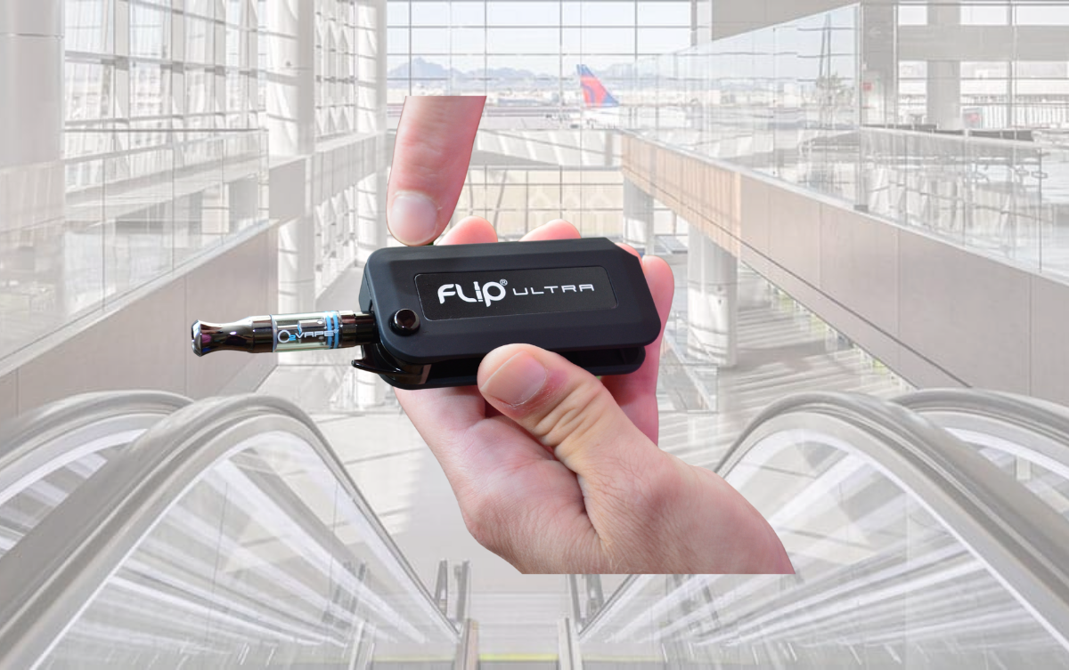 A vape being held in a hand with airport background